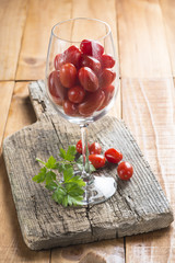 Copa de cristal con tomates cherry y perejil sobre madera