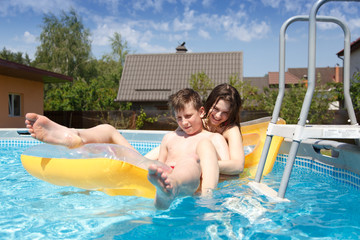 Two teenagers swimming in the pool