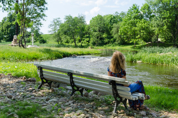 woman on bench admire fast flow river water stream