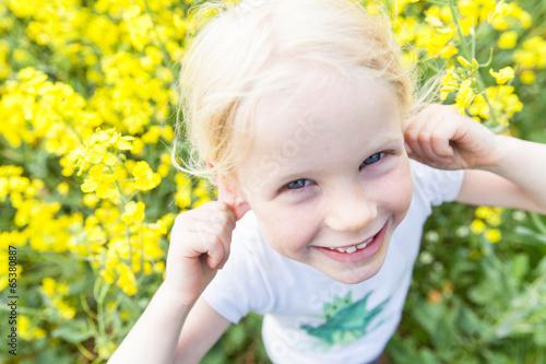 Leinwanddruck Bild Mädchen macht Faxen im Rapsfeld