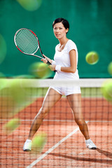 Sportswoman returning lots of balls at the tennis court