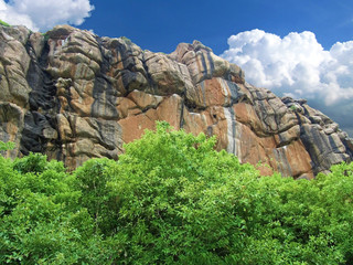 Eroded rock in India with trees at the bottom and blue sky