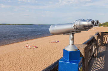 Coin operated binocular on the bank of river in summertime