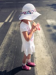 Girl drinking juice during crossing pedestrian crossing