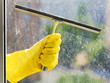hand in yellow glove washes window by squeegee