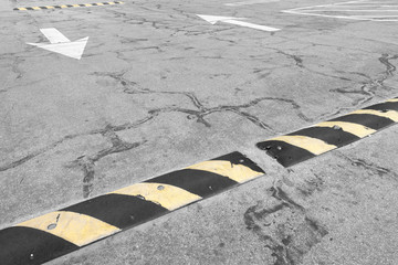 Traffic safety yellow and black speed bump in empty parking lot
