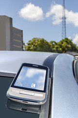 Cell phone on top of car roof, telecom tower background