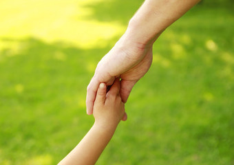 parent holds the hand of a small child