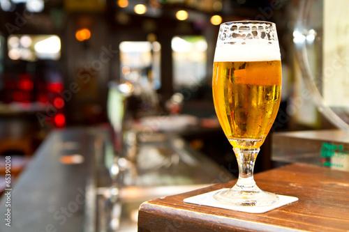 Keuken foto achterwand Bier / Cider Glass of light beer on a dark pub