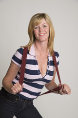 Woman in striped shirt wearing jeans and braces