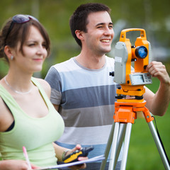 Two young land surveyors at work