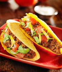 two beef tacos with cheese, lettuce and tomatos