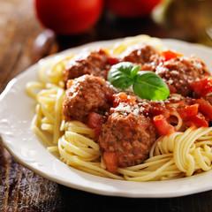 spaghetti and meatballs with basil garnish