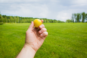 Hand with golf ball over a golf course
