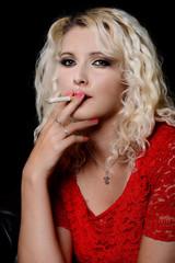 Belle jeune femme blonde fumant une cigarette