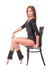 Attractive woman in gym suit sits on chair