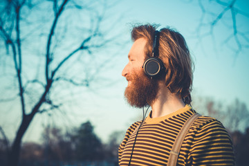 young bearded stylish handsome hipster man listening music
