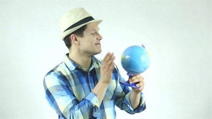 Attractive man holding a globe and pointing place