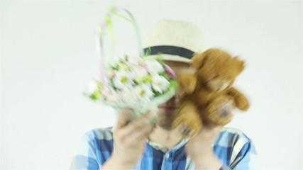 Young man in straw hat with flowers and teddy bear