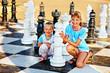 Children play chess outdoor.