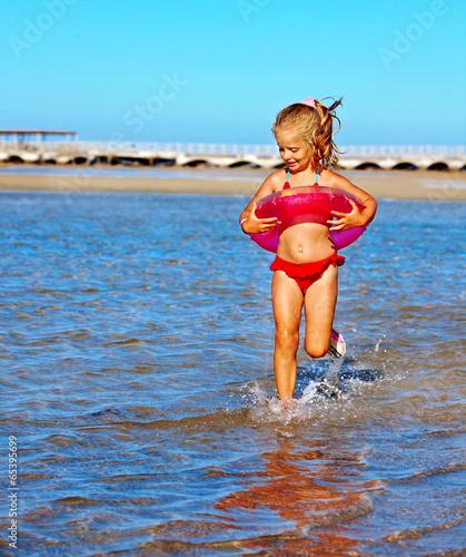 Child with beach ring running on  beach.