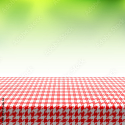 Picnic table covered with checkered tablecloth - 65397409