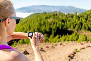 Cross country runner looking at sport watch