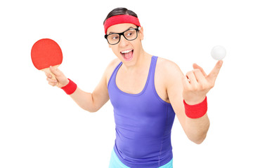 Young man holding a ball and a ping pong bat