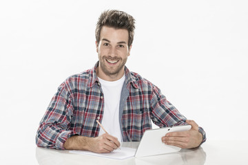 young man working with a digital tablet and a sheet of paper