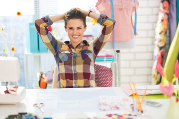 Portrait of relaxed seamstress in studio