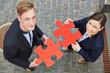 Mann und Frau halten rote Puzzleteile