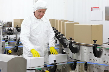 worker in apron, cap at production line in factory