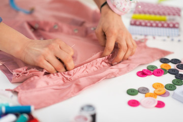Closeup on seamstress working with garment