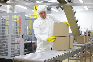 worker in white apron at packing line in factory