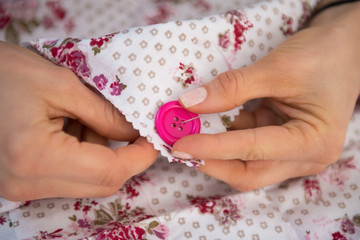 Closeup on seamstress sewing button