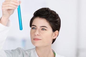 laborantin schaut prüfend auf eine blaue substanz