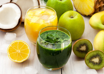 Green and orange smoothies with various fruit
