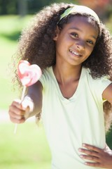 Young girl holding a heart lollipop in the park