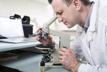 Doctor laboratory look in microscope