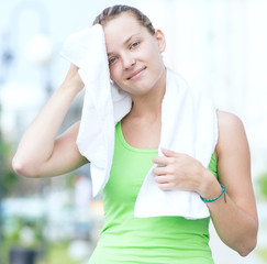 Tired woman after fitness time and exercising in city street par