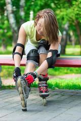 Girl going rollerblading sitting in bench putting on inline skat
