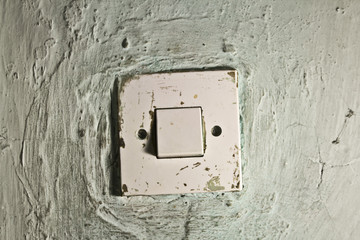 Old dirty light switch on old cracked wall