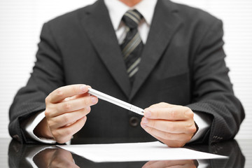 businessman holding pen over proposed contract and thinking abou