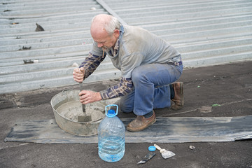 Man preparing mortar for repairing of roof's cement screed.