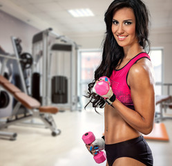 sporty woman with dumbbells in gym