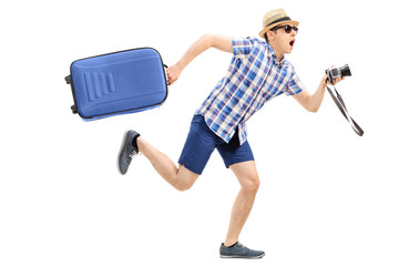 Male tourist rushing with his baggage and camera
