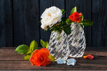 glass vases with white and orange roses in the old wooden table