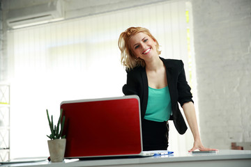 Young beautiful smiling woman leaning on the table in office