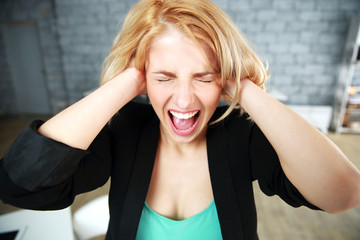 Screaming young woman with closed ears in office