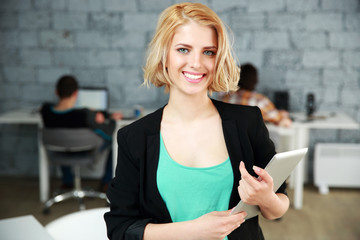 Young cheerful woman standing with tablet computer in office